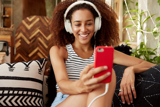 Beautiful young woman has afro hairstyle, makes video call via smart phone and headphones, speaks with friend online while sits at comfortable sofa with cushions. Free Photo