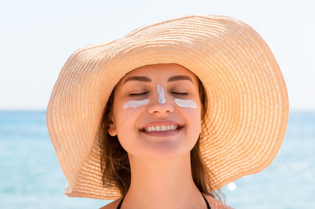 Beautiful young woman in hat is applying sunblock under her eyes and on her nose like indian. sun protection concept Premium Photo