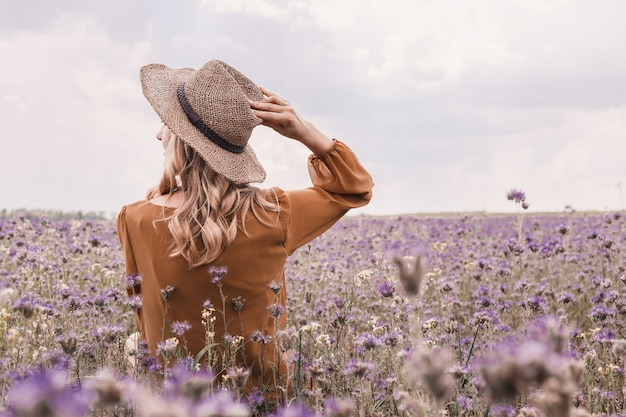 Beautiful young woman in hat in lavender field. blooming flowers Premium Photo