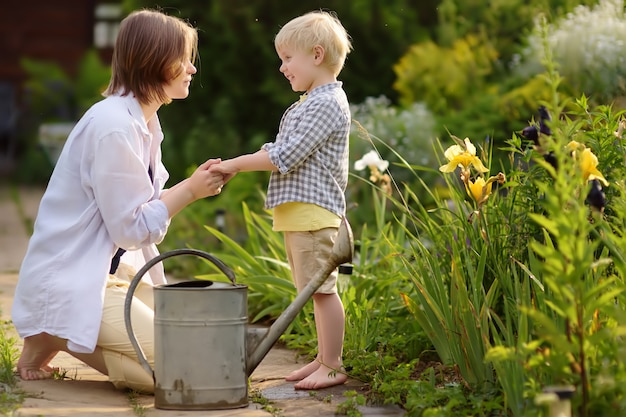 Beautiful young woman and her cute son watering plants in the garden at summer sunny day. Premium Photo