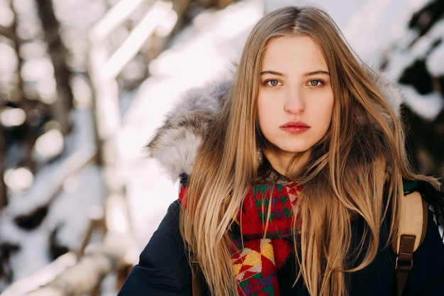 Beautiful young woman on a hike in a winter forest Premium Photo