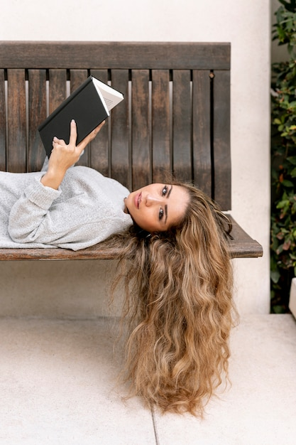 Beautiful young woman holding a book on a bench Free Photo