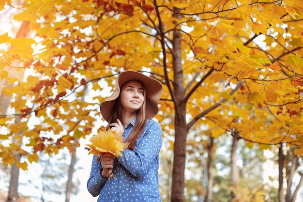 Beautiful young woman holding a bunch of autumn leaves Premium Photo