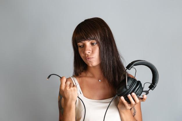 Красивая молодая женщина, держащая наушники и провод с разъемом на конце. Premium Фотографии