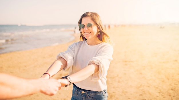 Beautiful young woman holding her boyfriend's hand at beach Free Photo