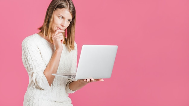 Beautiful young woman holding laptop on pink backdrop Free Photo