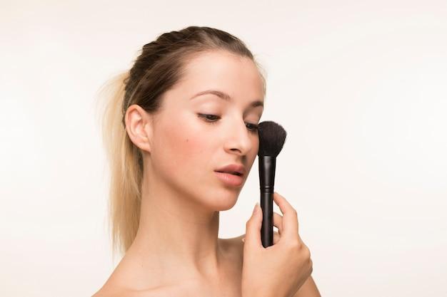 Beautiful young woman holding makeup brush Free Photo