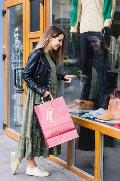 Beautiful young woman holding shopping bag pointing finger on window display Free Photo