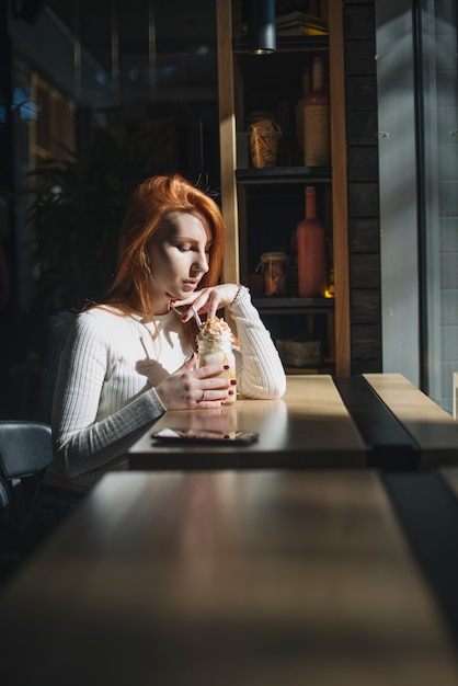 Beautiful young woman holding smoothie jar in the cafe Free Photo