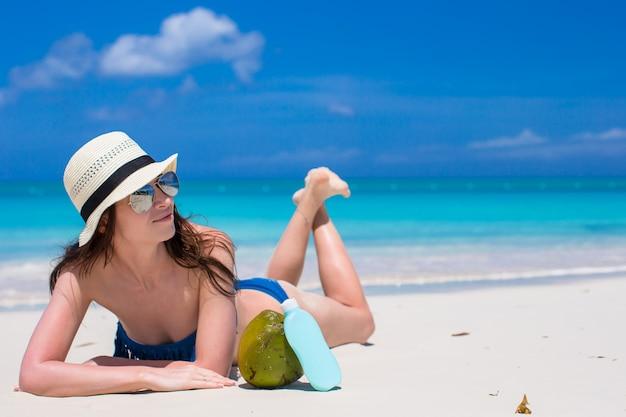 Beautiful young woman holding a suncream lying on tropical beach Premium Photo