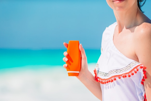 Beautiful young woman holding a suncream on tropical beach Premium Photo