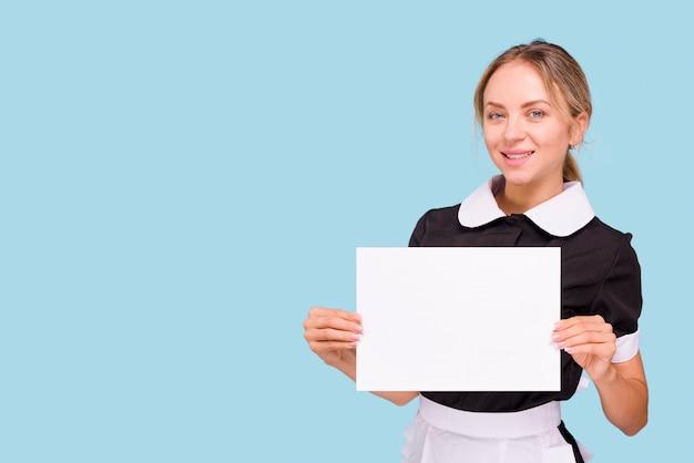 白い空白の紙を押しながら青い背景に提示する美しい若い女性 無料写真