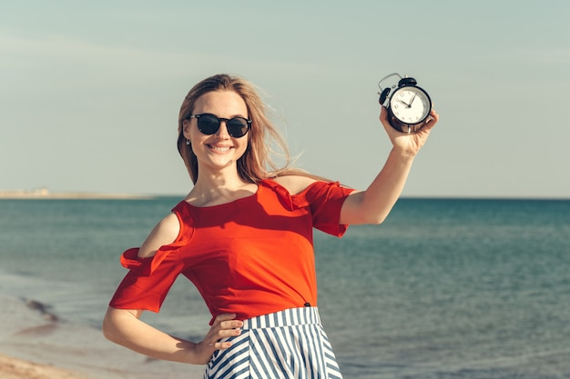 Beautiful young woman holds alarm clock on summer vacation. Premium Photo