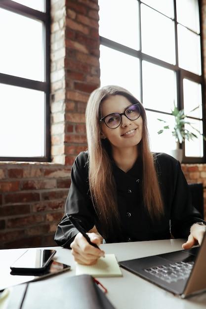 Bella giovane donna in ufficio a casa. lavorare da casa. concetto di telelavoro Foto Gratuite