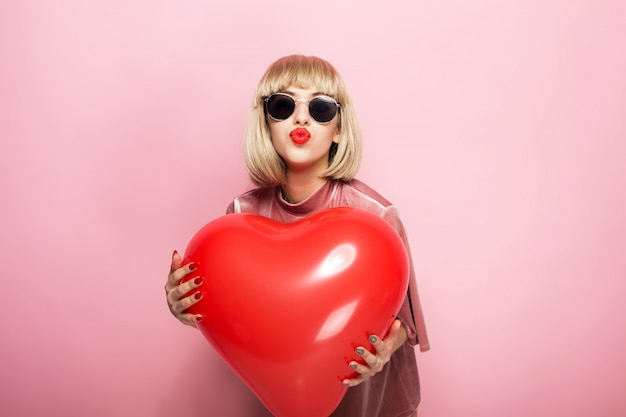 Beautiful young woman hugging in the shape of a heart a red ball and kisses. on a pink background. Premium Photo