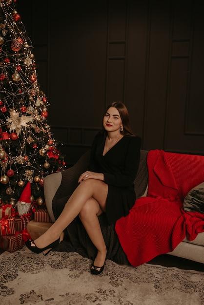 Красивая молодая женщина в черном платье возле елки в гирлянде Premium Фотографии