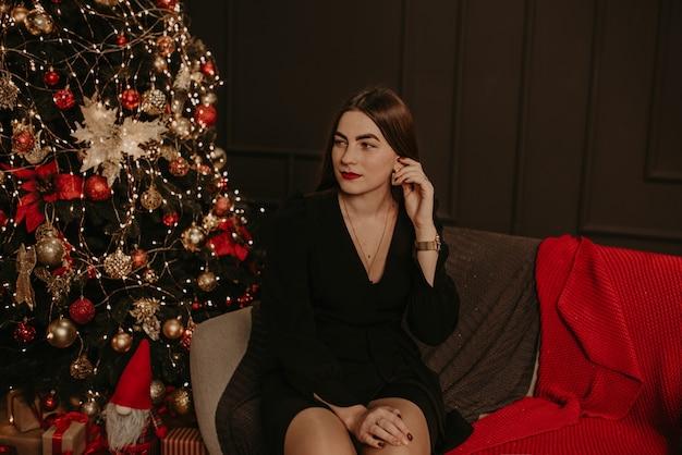 Красивая молодая женщина в черном платье возле елки в гирляндах Premium Фотографии
