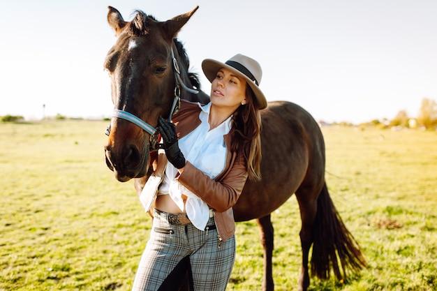 帽子と手袋、日没のフィールドでの茶色の馬の美しい若い女性 Premium写真