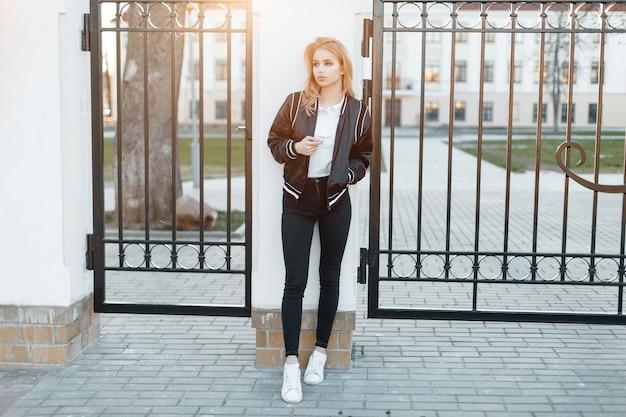 흰색 운동화에 유행 청바지에 흰색 폴로 셔츠에 세련된 검은 재킷에 아름 다운 젊은 여자는 일몰을 배경으로 금속 빈티지 게이트 근처에 서있다. 매력적인 소녀. 프리미엄 사진