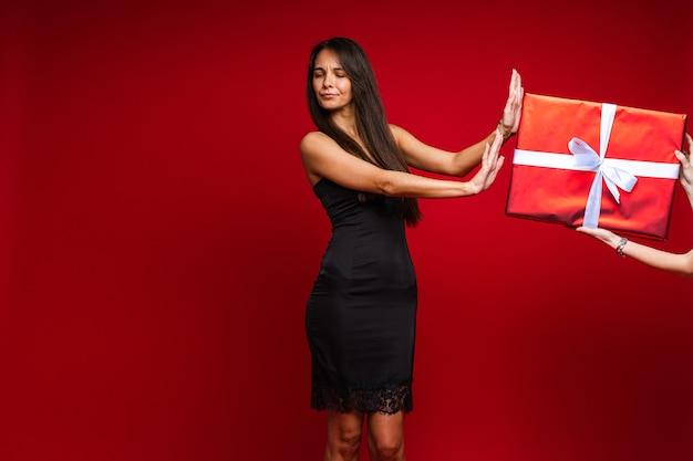 검은 드레스 저녁에 아름 다운 젊은 여자 광고 복사 공간이 빨간색 스튜디오 배경에 선물에서 거부 무료 사진