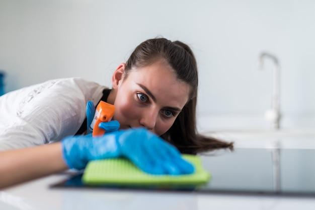 Красивая молодая женщина в защитных перчатках, очистка духовки с тряпкой Бесплатные Фотографии