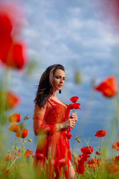 ケシ畑で赤の美しい若い女性 Premium写真
