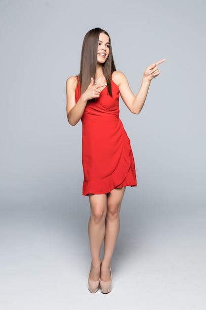 Красивая молодая женщина в красном мини-платье и высоких каблуках стоит, представляет что-то и смотрит в сторону. вид сбоку. выстрел в полный рост изолированный на белизне. Бесплатные Фотографии