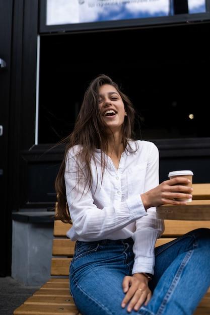 ストリートカフェの美しい若い女性は屋外のコーヒーを飲む 無料写真
