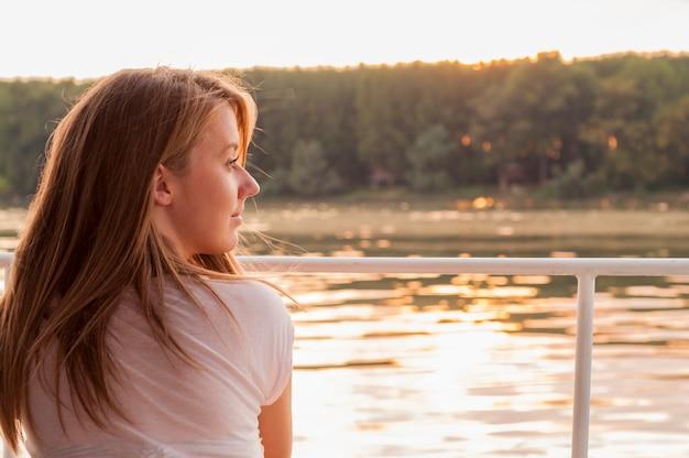 Красивая молодая женщина в белой одежде, сидя на берегу реки в Бесплатные Фотографии