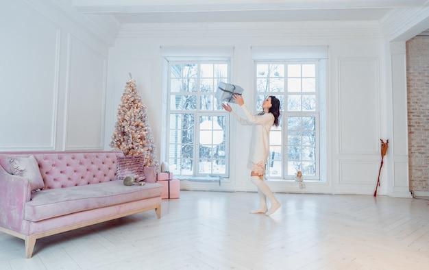 선물 상자와 함께 포즈를 취하는 하얀 드레스를 입고 아름 다운 젊은 여자 무료 사진