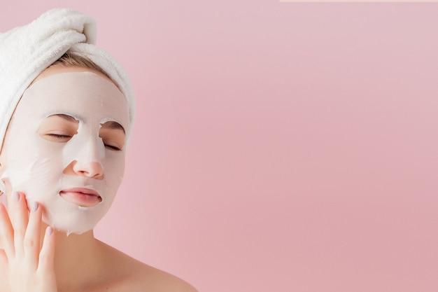 아름 다운 젊은 여자는 분홍색 공간에 얼굴에 화장품 티슈 마스크를 적용합니다 프리미엄 사진