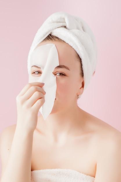 아름 다운 젊은 여자는 분홍색 얼굴에 화장품 티슈 마스크를 적용 프리미엄 사진