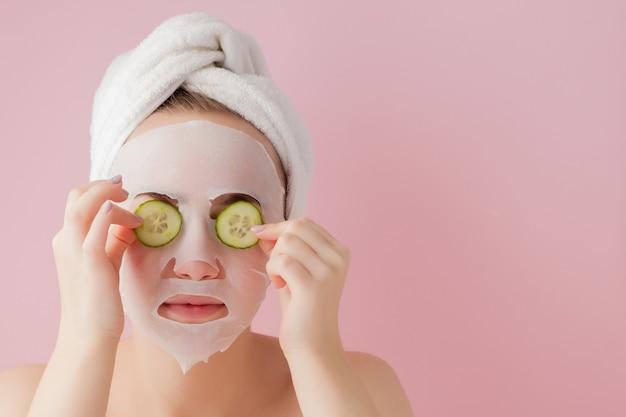 아름 다운 젊은 여자는 분홍색 공간에 오이와 얼굴에 화장품 티슈 마스크를 적용하고 있습니다 프리미엄 사진