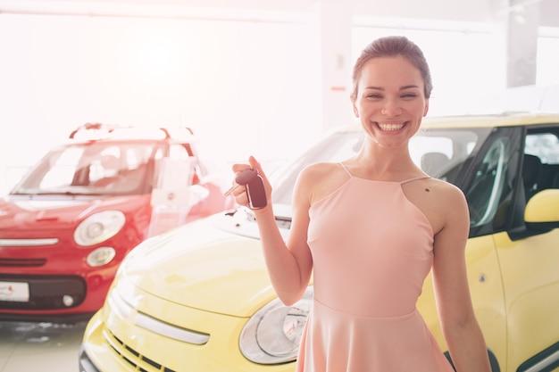 美しい若い女性が自動車販売店で鍵を握っています Premium写真