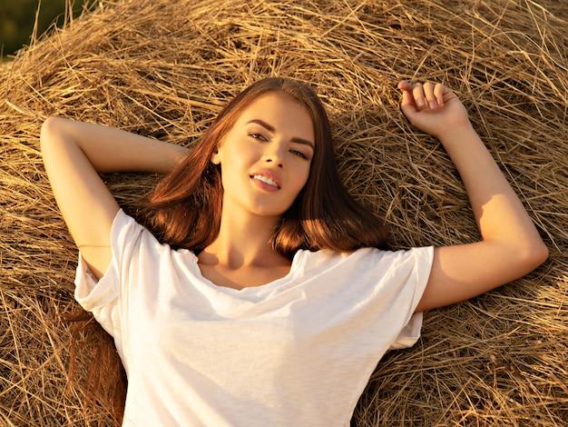 美しい若い女性は干し草の山でリラックスしています。美しいセクシーな女の子は自然にあります。長い茶色の髪の幸せなブルネットの少女。自然のかわいいモデルの肖像画。リラックスした夏の時間。 無料写真