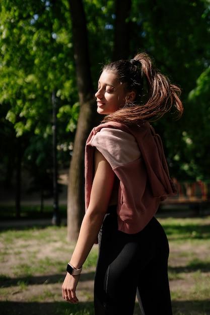 美しい若い女性は公園でジョギングした後休んでいます。 無料写真