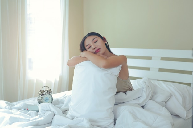 A beautiful young woman is sleeping and an alarm clock in the bedroom at home. Free Photo