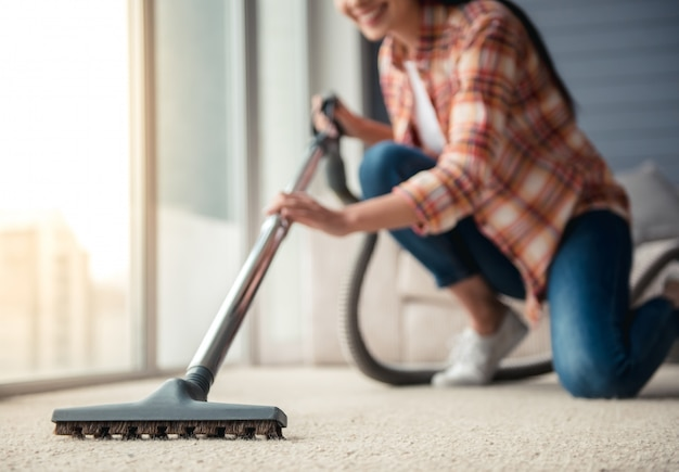 Beautiful young woman is smiling and using a vacuum. cleaning concept Premium Photo
