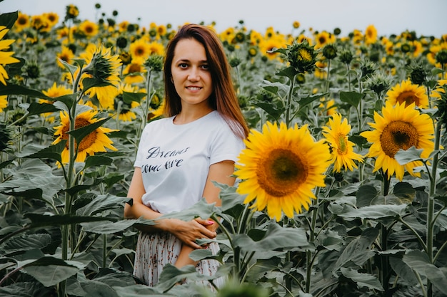 Beautiful young woman is standing in blooming sunflowers looking Premium Photo