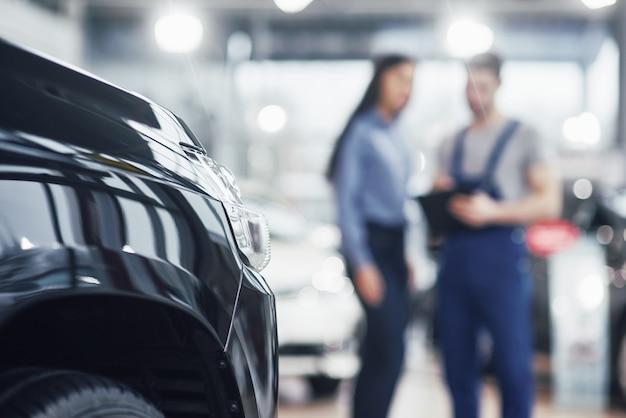 La bella giovane donna sta parlando al meccanico di automobile bello mentre ripara un'automobile in concessionaria Foto Gratuite