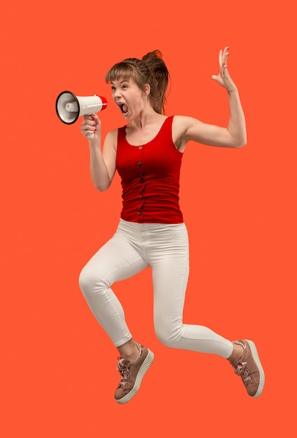 Bella giovane donna che salta con il megafono isolato su sfondo rosso. ragazza che corre in movimento o in movimento. le emozioni umane e il concetto di espressioni facciali Foto Gratuite