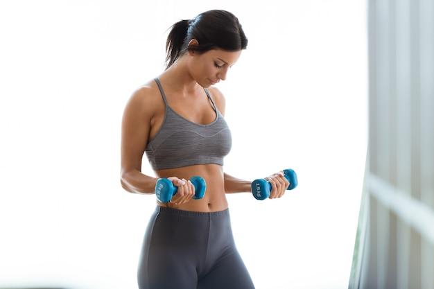Beautiful young woman lifting dumbbells at home. Free Photo