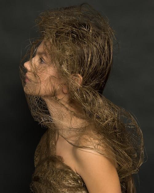 플라스틱 거미줄 사이에서 포즈를 취하는 동안 희망 측면에서 찾고 아름 다운 젊은 여자. 패션 사진 촬영, 플라스틱 금지, 폐기물 제로 개념. 세로 샷. 사진 닫기 프리미엄 사진