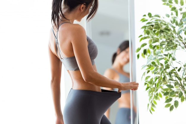 Beautiful young woman looking herself reflection in mirror at home. Free Photo
