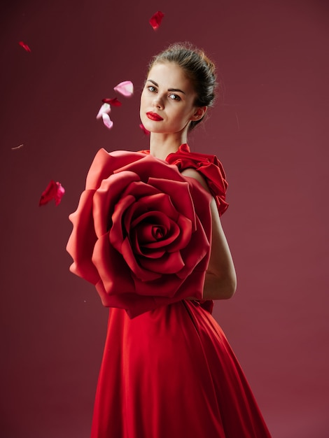 Beautiful young woman in a luxurious dress with roses, rose petals, stylish image, red lipstick Premium Photo