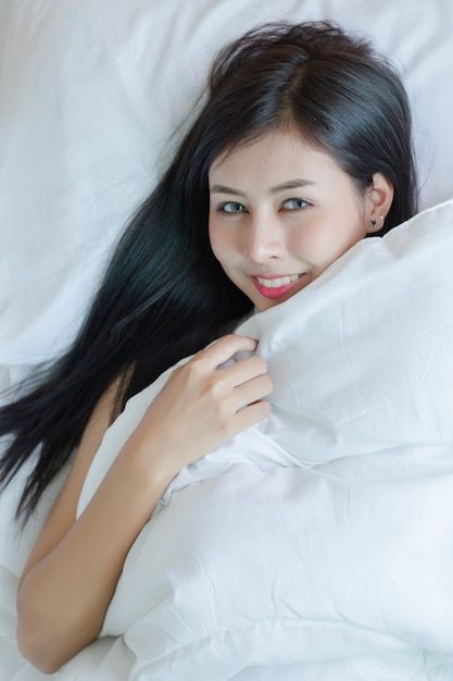 Beautiful young woman lying down in the bed. Free Photo