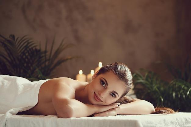 Bella giovane donna sdraiata e in attesa del suo massaggio. concetto di spa Foto Gratuite