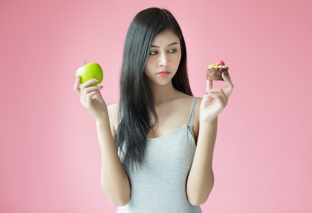 Beautiful young woman making a choice between a cake and apple Free Photo