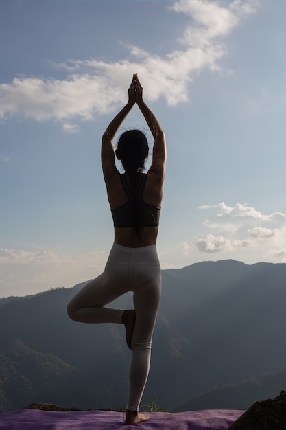 Beautiful young woman meditating and exercising on top of him. Free Photo