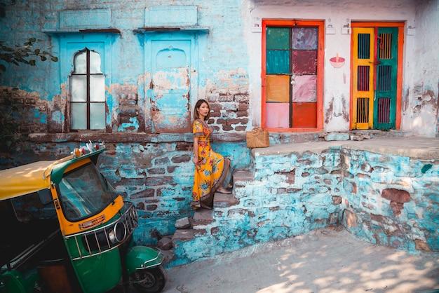 青い街の青/青緑色の背景に美しい若い女性。ジョードプル。インド Premium写真